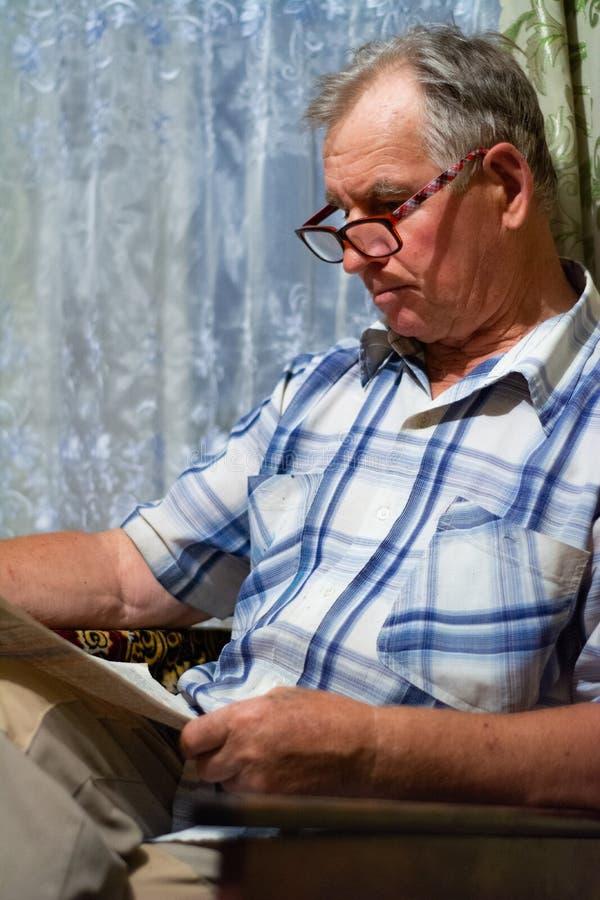 Ένα ηλικιωμένο άτομο κάθεται και διαβάζει μια εφημερίδα στοκ φωτογραφία