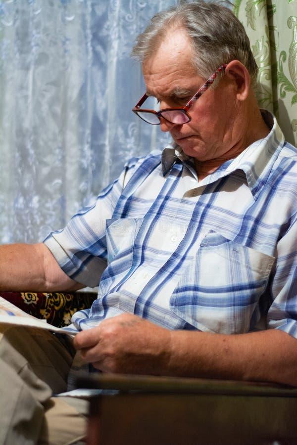 Ένα ηλικιωμένο άτομο κάθεται και διαβάζει μια εφημερίδα στοκ φωτογραφίες με δικαίωμα ελεύθερης χρήσης