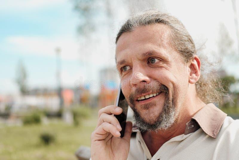 Ένα ηλικιωμένο όμορφο άτομο με μακρυμάλλη στην ουρά μιλά συναισθηματικά σε ένα τηλέφωνο κυττάρων σε ένα πάρκο σε έναν πάγκο στοκ φωτογραφία με δικαίωμα ελεύθερης χρήσης