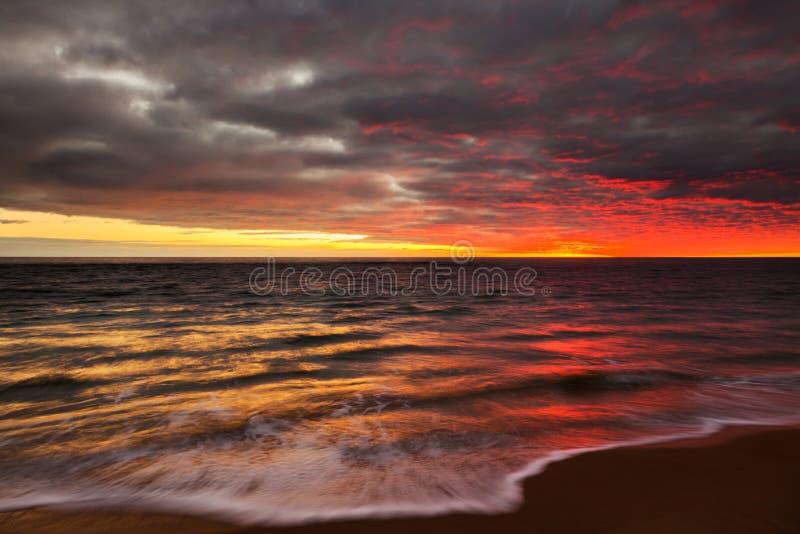 Ένα ηλιοβασίλεμα πέρα από την εξέταση το νερό την παραλία Noarlunga λιμένων στοκ εικόνες