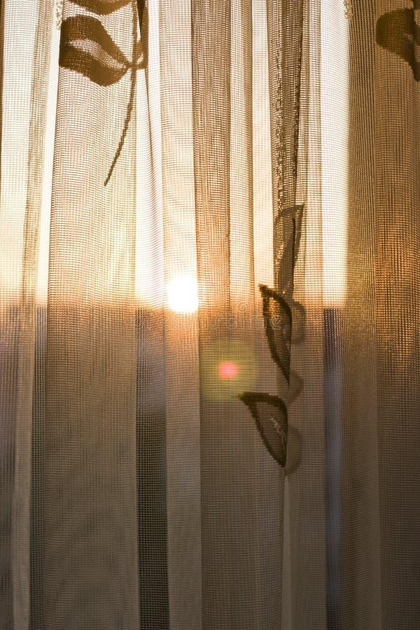 Ένα ηλιοβασίλεμα που βλέπει όμορφο μέσω ενός παραθύρου με μια κουρτίνα στοκ εικόνες