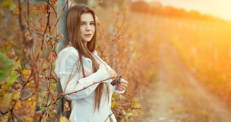 Ένα ημίγυμνο κορίτσι brunette σε μια άσπρη εκλεκτής ποιότητας μπλούζα και μακρυμάλλης τοποθέτηση στα πλαίσια ενός αμπελώνα φθινοπ στοκ εικόνες
