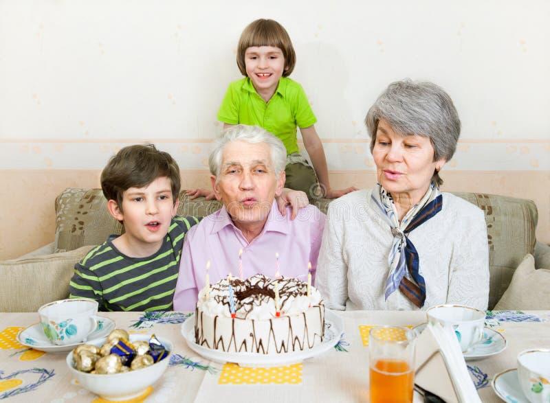 Ένα ηλικιωμένο ζεύγος εκρήγνυται τα κεριά σε ένα κέικ στοκ εικόνες