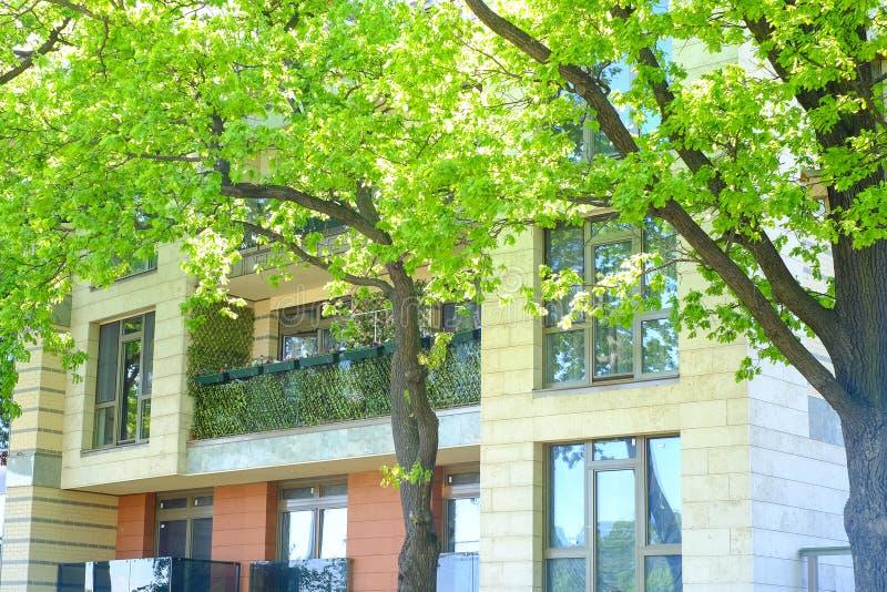 Ένα θερινό ενοικιαζόμενο δωμάτιο μπαλκόνια στις εγκαταστάσεις με τα λουλούδια περπάτημα στη δροσερή σκιά των δέντρων στοκ εικόνες