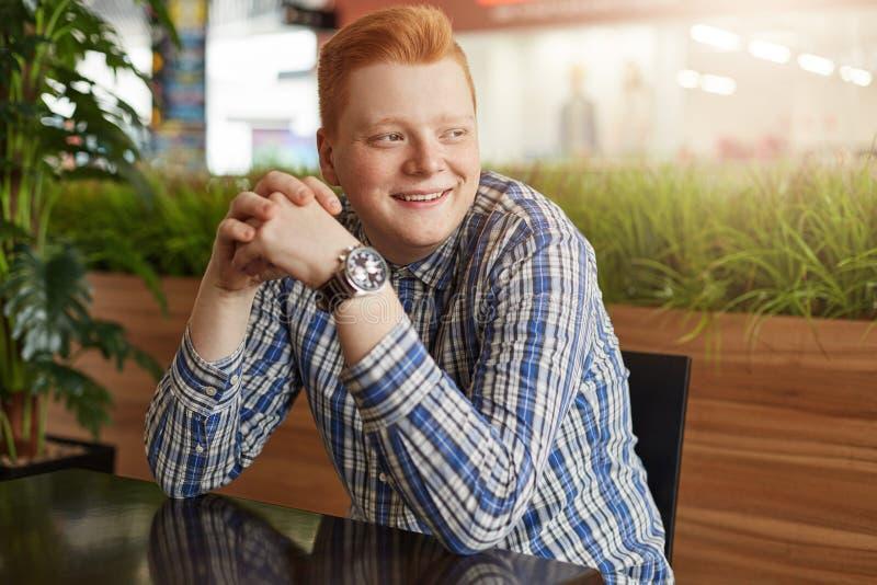 Ένα θετικό redhead hipster με τις φακίδες που φορούν τη μοντέρνη ελεγχμένη συνεδρίαση πουκάμισων και ρολογιών στον ξύλινο πίνακα  στοκ φωτογραφία με δικαίωμα ελεύθερης χρήσης