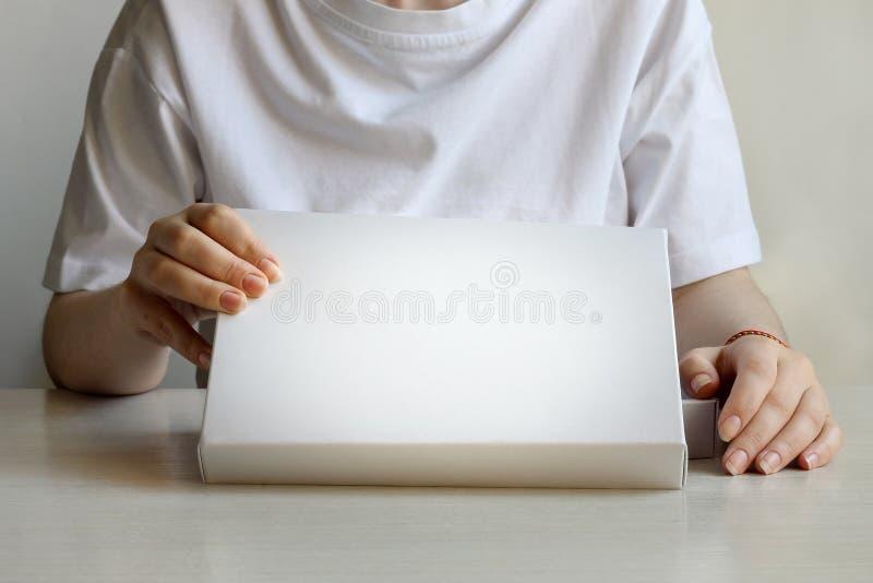Ένα θηλυκό, γυναίκα, κορίτσι δύο χέρια κρατά και ανοίγει το κενό άσπρο λευκό κιβωτίων στοκ εικόνες με δικαίωμα ελεύθερης χρήσης