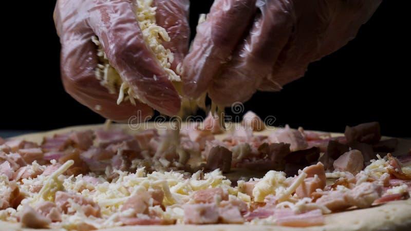 Ένα θηλυκό παραδίδει τα μαγειρεύοντας γάντια που ψεκάζουν την πίτσα με το ξυμένο τυρί, ιταλική έννοια τροφίμων Πλαίσιο Κλείστε επ στοκ εικόνες