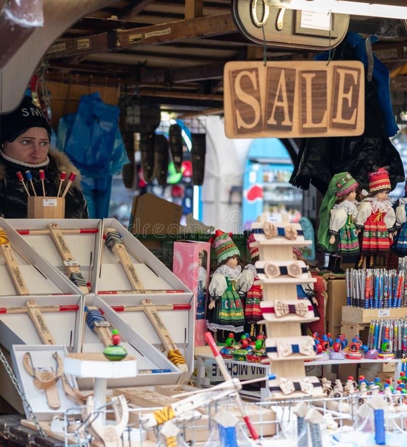 Ένα θηλυκό πωλεί τα αναμνηστικά και άλλα trinkets στους τουρίστες από έναν στάβλο στη μέση της Πράγας στοκ εικόνα