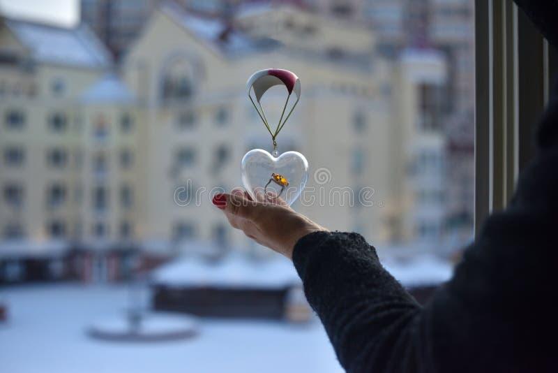 Ένα θηλυκό χέρι κρατά μια διαφανή καρδιά γυαλιού με ένα μεγάλο δαχτυλίδι μέσα στοκ φωτογραφία
