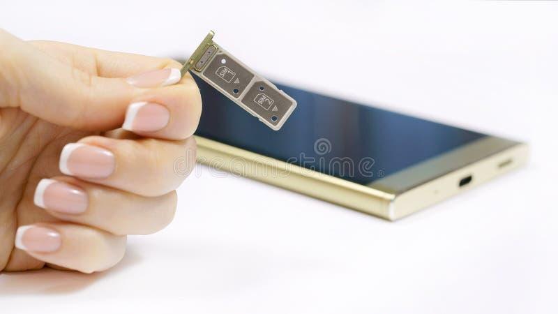 ένα θηλυκό χέρι κρατά μια διπλή υποδοχή κάρτας SIM στοκ φωτογραφία