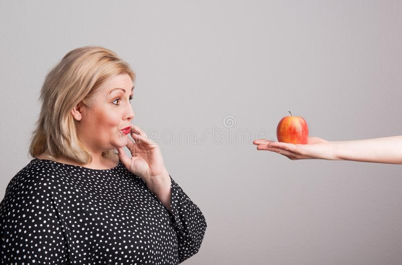 Ένα θηλυκό χέρι που δίνει ένα μήλο σε μια ελκυστική υπέρβαρη γυναίκα στο στούντιο στοκ εικόνες με δικαίωμα ελεύθερης χρήσης