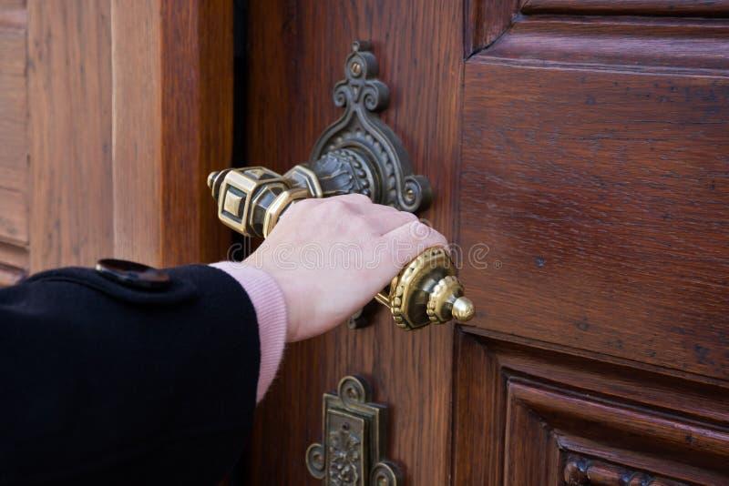 Ένα θηλυκό χέρι που κρατά έναν στρόφαλο από μια παλαιά ξύλινη πόρτα στοκ εικόνες με δικαίωμα ελεύθερης χρήσης