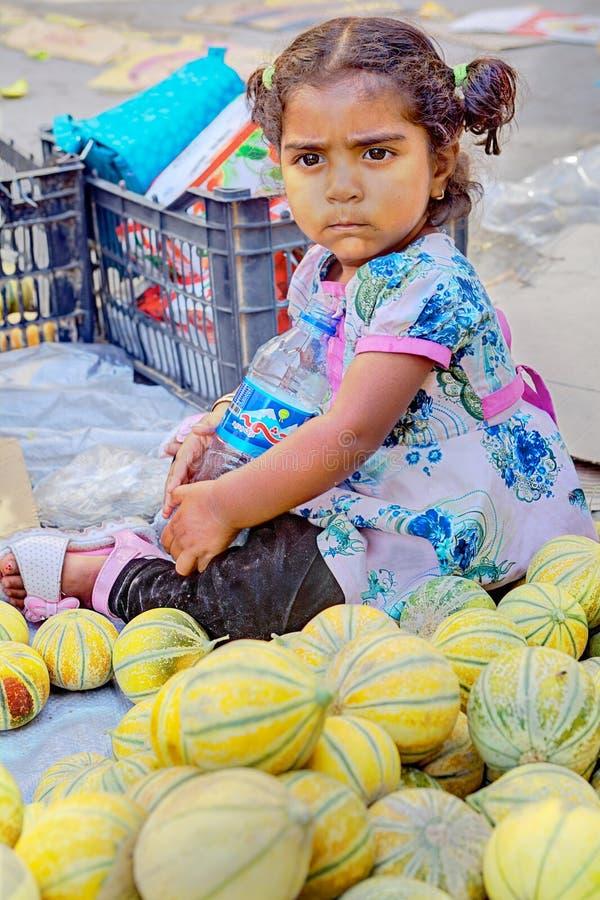 Ένα θλιβερό μικρό κορίτσι κάθεται στο πεζοδρόμιο κοντά στα πεπόνια στοκ εικόνα