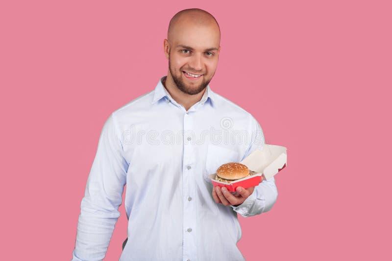 Ένα ικανοποιημένο άτομο με μια πολύβλαστη γενειάδα και ένα φαλακρό κεφάλι, κρατά burger στο χέρι του και εξετάζει τη κάμερα στάση στοκ φωτογραφία με δικαίωμα ελεύθερης χρήσης