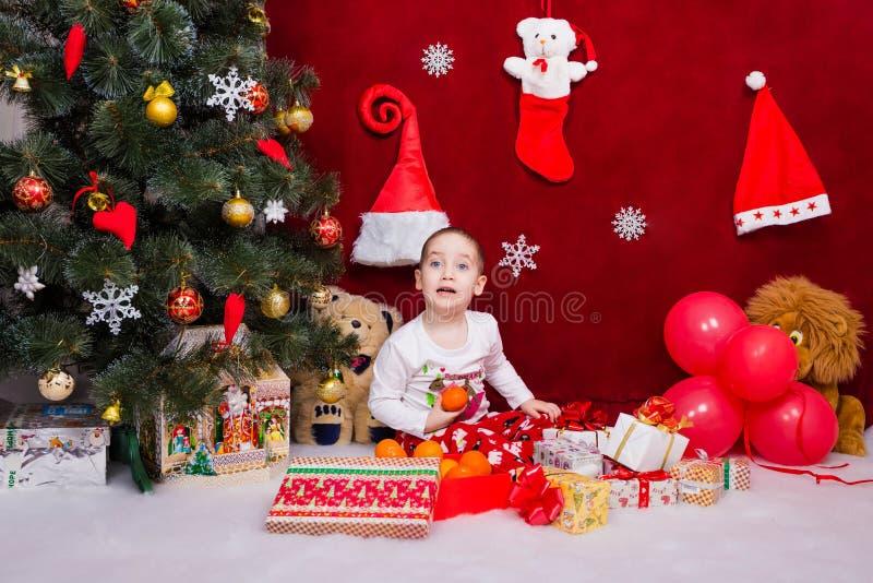 Ένα ικανοποιημένο παιδί έλαβε τα δώρα για τα Χριστούγεννα στοκ εικόνες