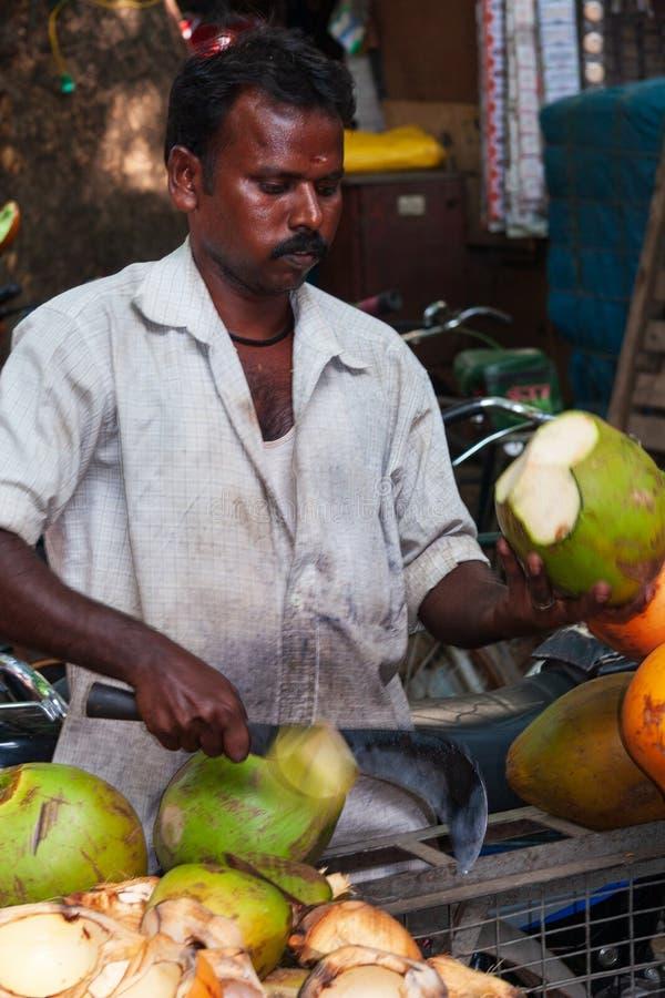 Ένα ινδικό άτομο κόβει μια νέα πράσινη καρύδα με έναν αιχμηρό μπαλτά FO στοκ εικόνες με δικαίωμα ελεύθερης χρήσης
