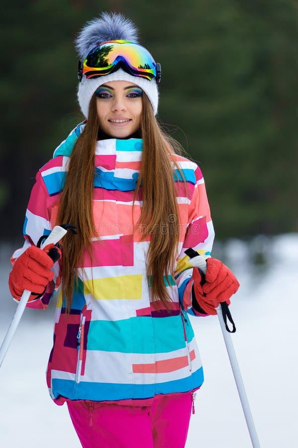 Ένα κάνοντας σκι κορίτσι στα φωτεινά αθλητικά ενδύματα στοκ φωτογραφίες