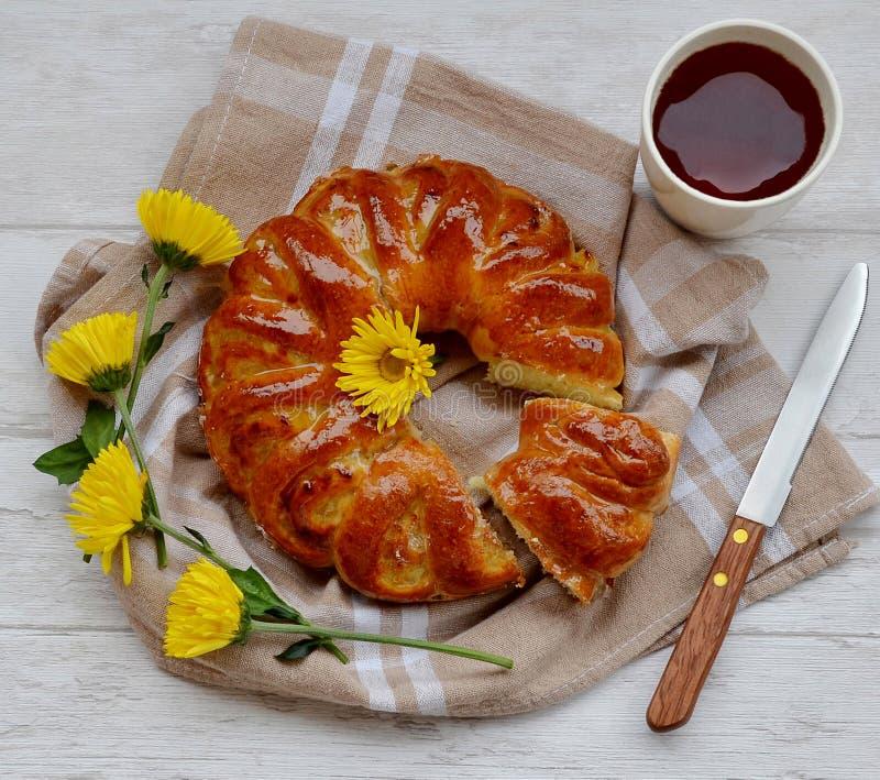 Ένα κέικ, ένα φλιτζάνι του καφέ και λουλούδια στον πίνακα στοκ εικόνα με δικαίωμα ελεύθερης χρήσης