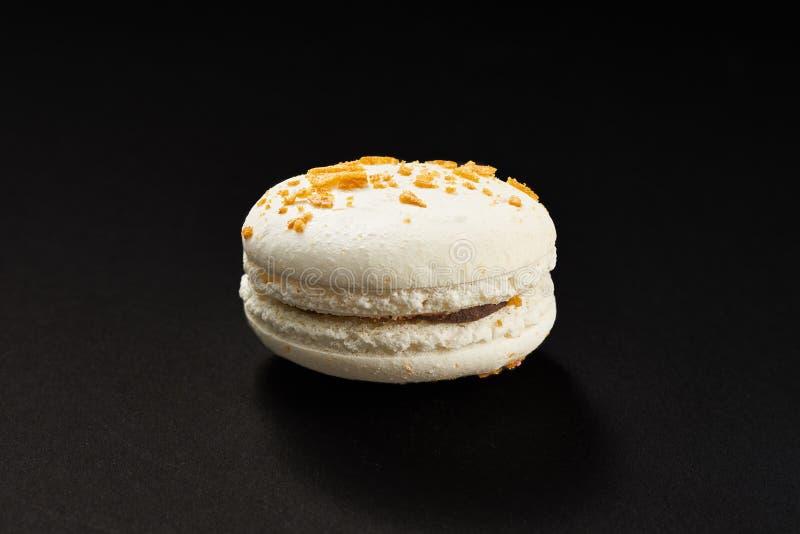 Ένα κέικ του άσπρου χρώματος μακαρονιών Εύγευστο macaroon καραμέλας που απομονώνεται στο μαύρο υπόβαθρο Γαλλικό γλυκό μπισκότο στοκ φωτογραφίες με δικαίωμα ελεύθερης χρήσης