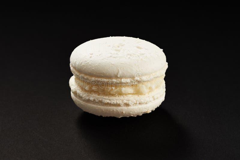 Ένα κέικ του άσπρου χρώματος μακαρονιών Εύγευστο macaroon καρύδων που απομονώνεται στο μαύρο υπόβαθρο Γαλλικό γλυκό μπισκότο στοκ εικόνες με δικαίωμα ελεύθερης χρήσης