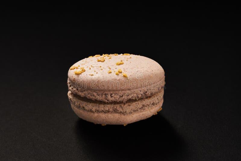 Ένα κέικ του καφετιού χρώματος μακαρονιών Εύγευστο macaroon σοκολάτας που απομονώνεται στο μαύρο υπόβαθρο Γαλλικό γλυκό μπισκότο στοκ εικόνες με δικαίωμα ελεύθερης χρήσης
