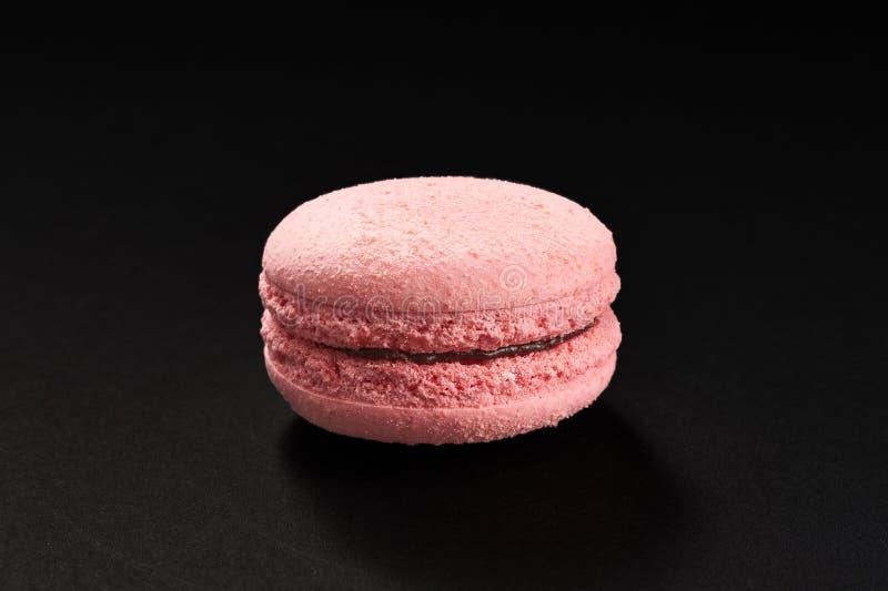 Ένα κέικ του ρόδινου χρώματος μακαρονιών Εύγευστο macaroon φραουλών που απομονώνεται στο μαύρο υπόβαθρο Γαλλικό γλυκό μπισκότο στοκ εικόνες
