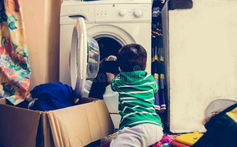 Ένα και το αγοράκι μισού χρονών που βάζει τα ενδύματα στο πλυντήριο στοκ εικόνες