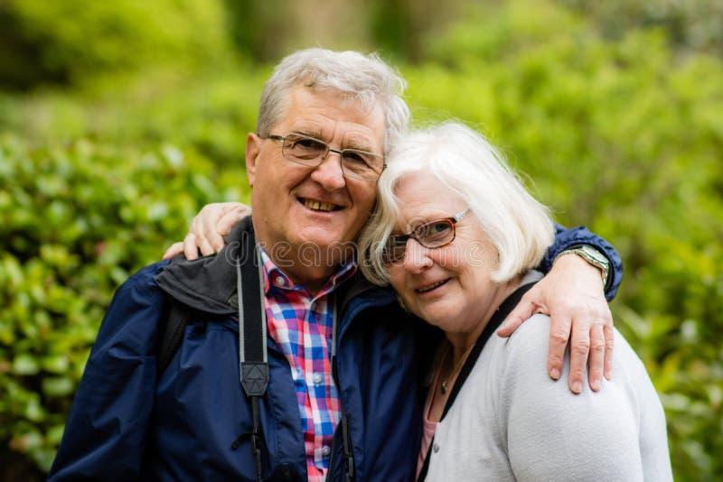 Ένα καλό ηλικιωμένο ζεύγος, που αγκαλιάζει και που χαμογελά στη κάμερα στοκ εικόνες