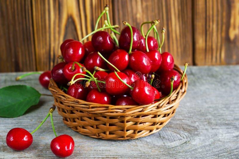 Ένα καλάθι με τα cherrys στον ξύλινο πίνακα στοκ φωτογραφία με δικαίωμα ελεύθερης χρήσης