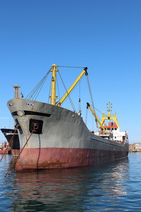 Ένα κενό ξηρό σκάφος εμπορευματοκιβωτίων φορτίου που βλέπει από την παραλία από την πλευρά τόξων λιμένων του σκάφους με άλλο πίσω στοκ φωτογραφίες