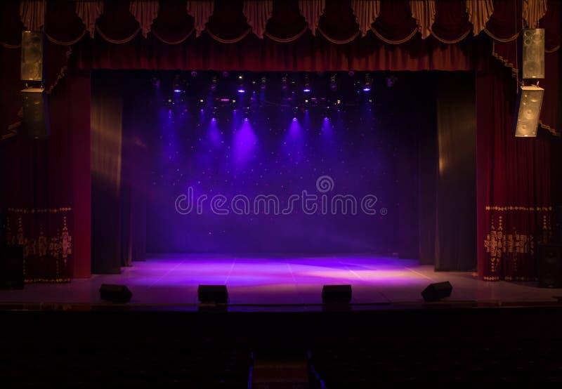 Ένα κενό στάδιο του θεάτρου, αναμμένο από τα επίκεντρα και τον καπνό στοκ εικόνες