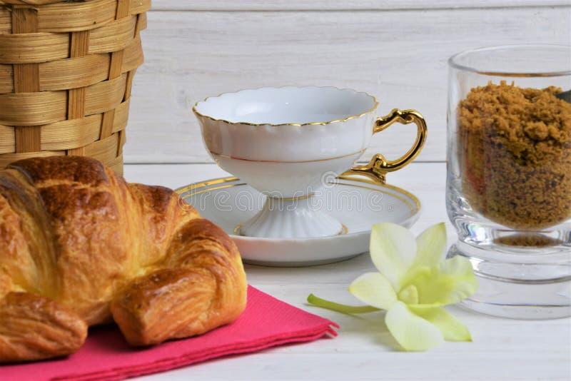 Ένα κενό φλυτζάνι καφέ σε ένα πιατάκι, Croissant, καλάθι στοιχείων, λουλούδι, καφετιά ζάχαρη σε ένα ξύλινο χρωματισμένο υπόβαθρο στοκ φωτογραφίες