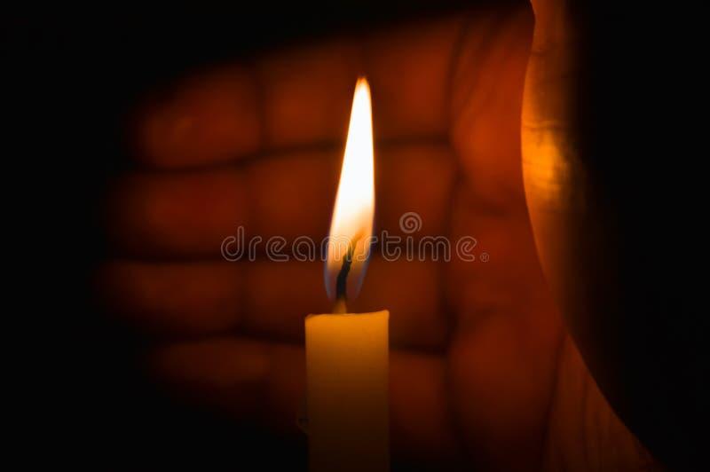 Ένα κερί που προστατεύεται αναμμένο από τον αέρα από ένα χέρι στοκ φωτογραφία με δικαίωμα ελεύθερης χρήσης