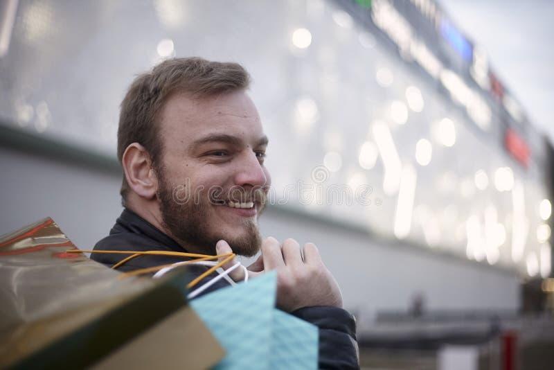 ένα κεφάλι προσώπου νεαρών άνδρων, 20-29 χρονών, που κοιτάζει λοξά Φέρνοντας τσάντες αγορών στα χέρια του στοκ φωτογραφία με δικαίωμα ελεύθερης χρήσης