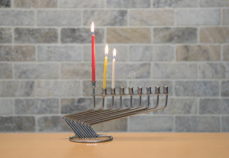 Ένα κηροπήγιο μετάλλων για τον εορτασμό Hanukkah στέκεται με τα αναμμένα κεριά στον πίνακα ενάντια στο σκηνικό ενός τουβλότοιχος στοκ εικόνες με δικαίωμα ελεύθερης χρήσης