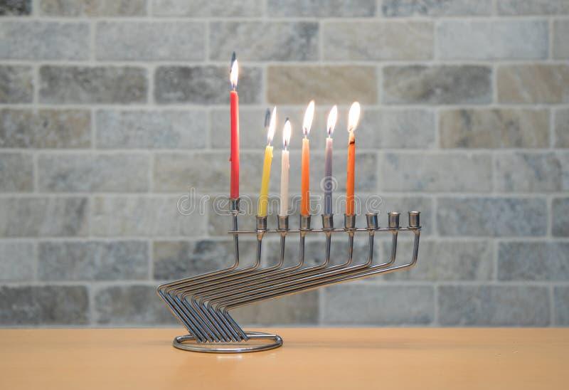 Ένα κηροπήγιο μετάλλων για τον εορτασμό Hanukkah στέκεται με τα αναμμένα κεριά στον πίνακα ενάντια στο σκηνικό ενός τουβλότοιχος στοκ εικόνες