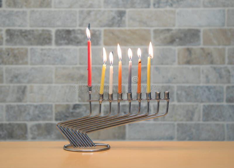 Ένα κηροπήγιο μετάλλων για τον εορτασμό Hanukkah στέκεται με τα αναμμένα κεριά στον πίνακα ενάντια στο σκηνικό ενός τουβλότοιχος στοκ εικόνα