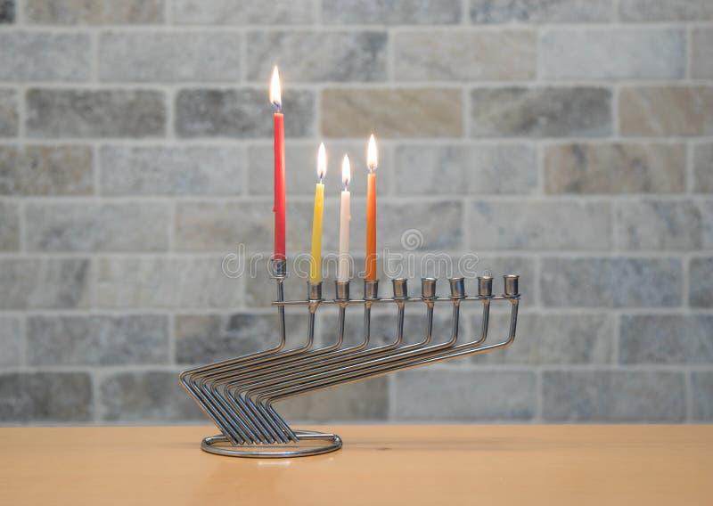 Ένα κηροπήγιο μετάλλων για τον εορτασμό Hanukkah στέκεται με τα αναμμένα κεριά στον πίνακα ενάντια στο σκηνικό ενός τουβλότοιχος στοκ φωτογραφία