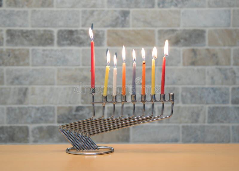 Ένα κηροπήγιο μετάλλων για τον εορτασμό Hanukkah στέκεται με τα αναμμένα κεριά στον πίνακα ενάντια στο σκηνικό ενός τουβλότοιχος στοκ εικόνα με δικαίωμα ελεύθερης χρήσης
