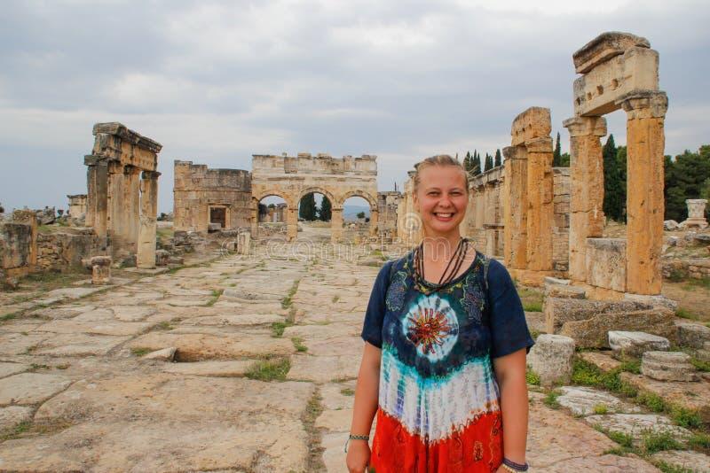 Ένα κλασικό παλαιό ελληνικό θέατρο σε Pamukkale, Denizli, η Τουρκία και μια λευκιά νέα γυναίκα σε έναν χίπη ντύνουν στοκ εικόνα