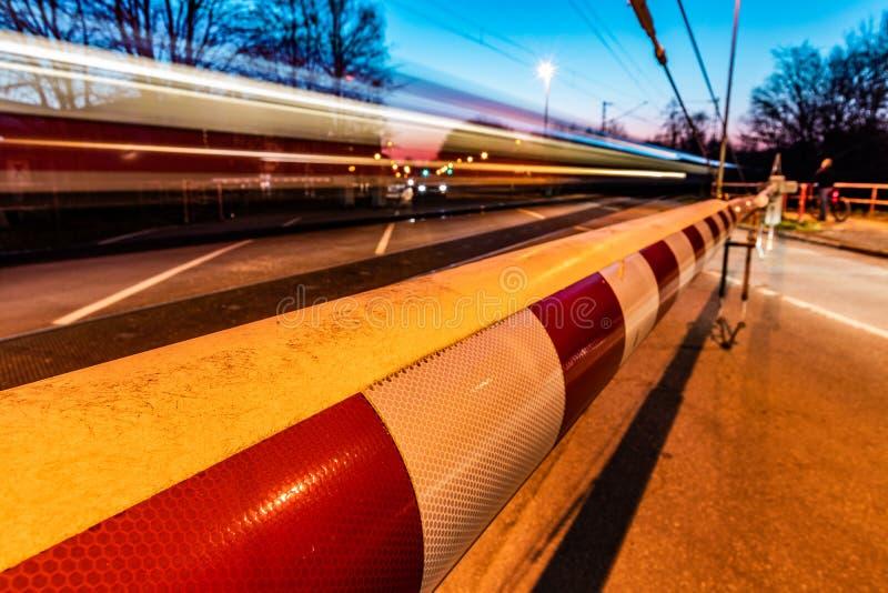 Ένα κλειστό εμπόδιο σιδηροδρόμων στη Γερμανία με ένα τραίνο στην κίνηση και την αναμονή αυτοκινήτων στοκ εικόνα