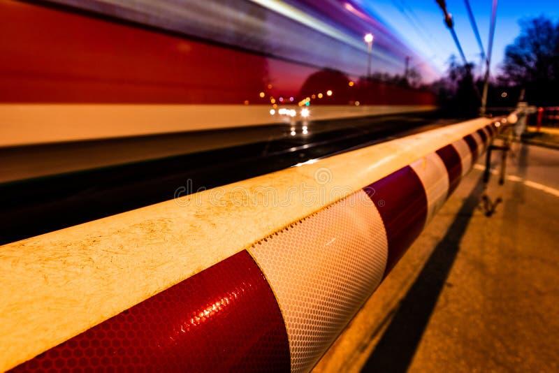 Ένα κλειστό εμπόδιο σιδηροδρόμων στη Γερμανία με ένα τραίνο στην κίνηση και την αναμονή αυτοκινήτων στοκ φωτογραφίες