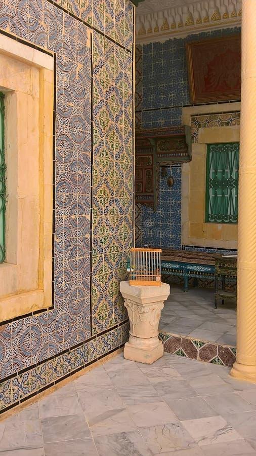 Ένα κλουβί με ένα καναρίνι σε ένα μαρμάρινο βάθρο στο προαύλιο ενός αραβικού σπιτιού στοκ φωτογραφία