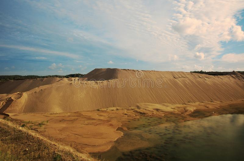 Ένα κοίλωμα αμμοχάλικου με τα βουνά άμμων και μια τεχνητή λίμνη στοκ εικόνες