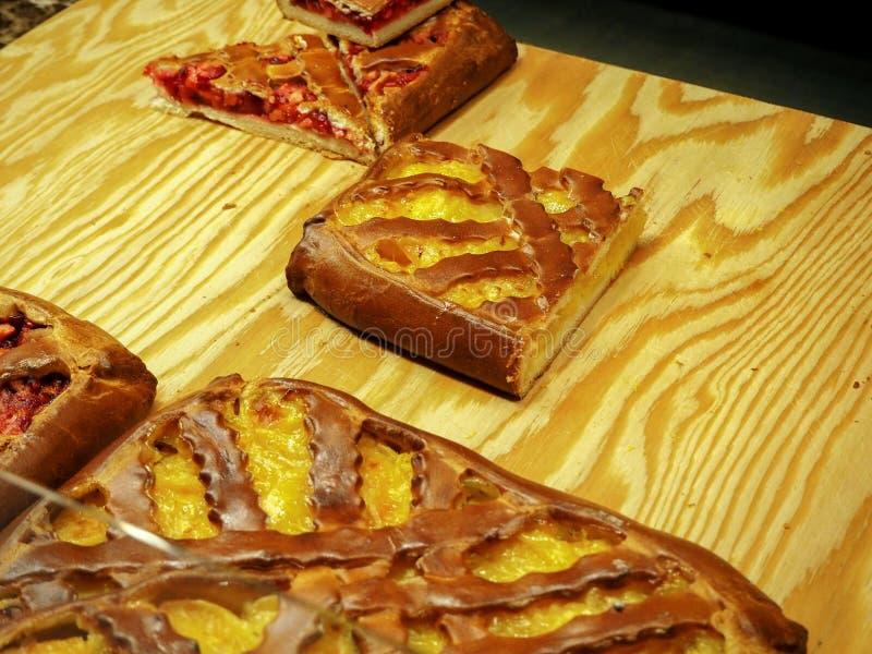 Ένα κομμάτι της πίτας φρούτων με μια κίτρινη και κόκκινη πλήρωση σε έναν ξύλινο πίνακα στοκ φωτογραφία με δικαίωμα ελεύθερης χρήσης