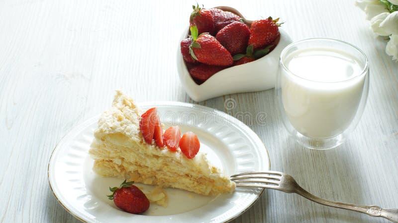 Ένα κομμάτι του κέικ Napoleon και ενός καρδιά-διαμορφωμένου κύπελλου με μια κόκκινη φράουλα, ένα γυαλί δίπλα στο γάλα, μια ελαφρι στοκ φωτογραφία με δικαίωμα ελεύθερης χρήσης