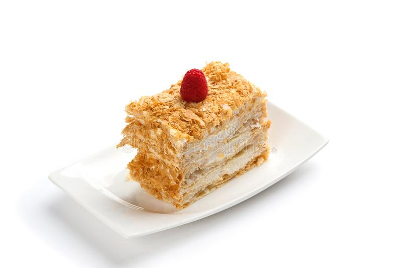 Ένα κομμάτι του κέικ napoleon που διακοσμείται με το σμέουρο σε ένα άσπρο ορθογώνιο πιάτο σε ένα απομονωμένο άσπρο υπόβαθρο στοκ εικόνες