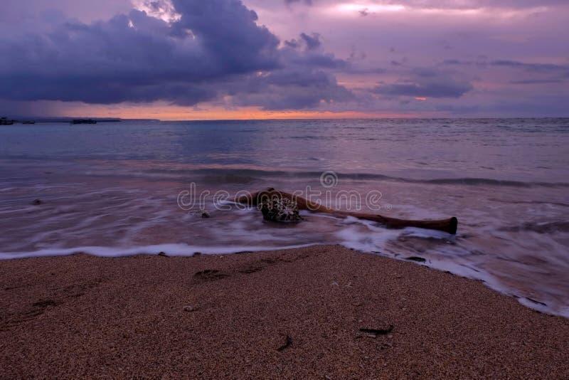 Ένα κομμάτι του ξύλου στην άμμο της παραλίας Kuta Μπαλί στο σούρουπο στοκ φωτογραφία με δικαίωμα ελεύθερης χρήσης