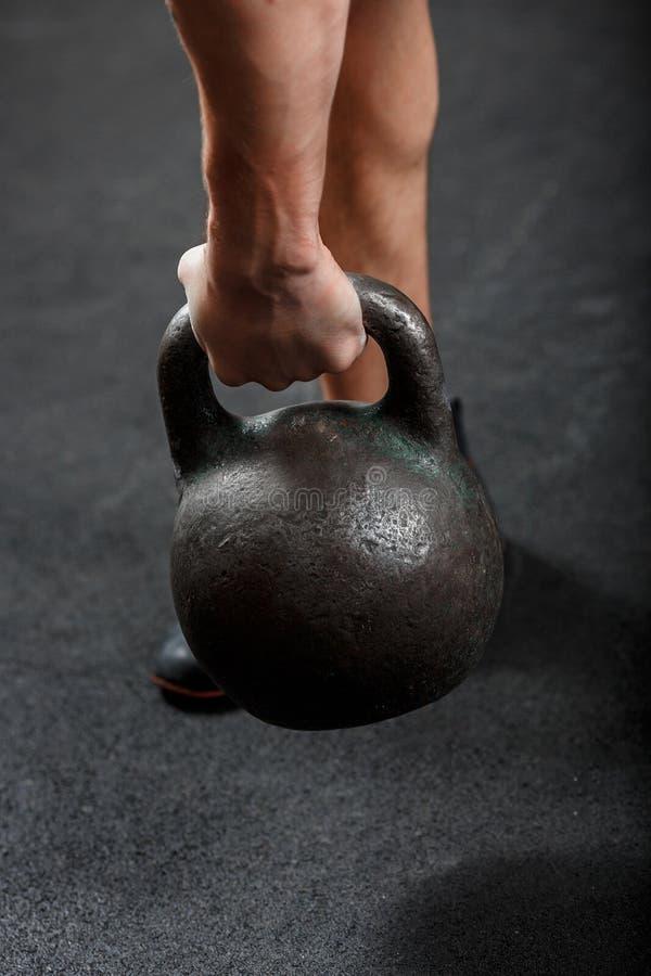 Ένα κομμάτι του χεριού του ανθρώπου, σηκώνοντας μαύρο γυμναστικό κουδουνάκι στοκ φωτογραφία με δικαίωμα ελεύθερης χρήσης