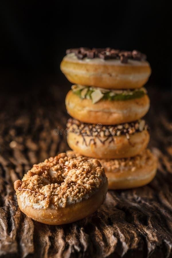 Ένα κομμάτι doughnut στην ξύλινη σανίδα με έναν σωρό των donuts πίσω στο σκοτεινό υπόβαθρο στοκ εικόνες